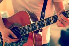 Verwijderd van een jonge mens die een zonnestraal westelijke gitaar spelen royalty-vrije stock afbeelding