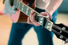 Verwijderd van een jonge mens die een zonnestraal westelijke gitaar spelen stock afbeeldingen