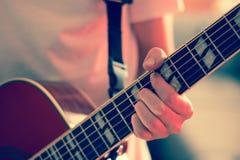Verwijderd van een jonge mens die een zonnestraal westelijke gitaar spelen royalty-vrije stock fotografie