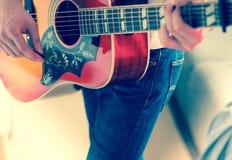 Verwijderd van een jonge mens die een zonnestraal westelijke gitaar spelen royalty-vrije stock foto