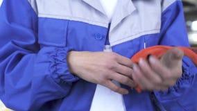 Verwijdert de auto mechanische specialist vuile oranje handschoenen na het werk met machines en toont vuil mazol indient stock footage