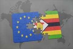 verwirren Sie mit der Staatsflagge der Europäischer Gemeinschaft und des Simbabwes auf einem Weltkartehintergrund Lizenzfreie Stockfotos