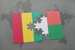 verwirren Sie mit der Staatsflagge der Guine und des Madagaskars auf einer Weltkarte lizenzfreie abbildung