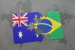 verwirren Sie mit der Staatsflagge von Australien und von Brasilien auf einem Weltkartehintergrund Lizenzfreies Stockbild