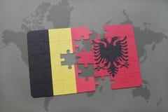 verwirren Sie mit der Staatsflagge von Belgien und von Albanien auf einem Weltkartehintergrund Lizenzfreie Stockbilder