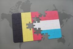 verwirren Sie mit der Staatsflagge von Belgien und von Luxemburg auf einem Weltkartehintergrund Stockfoto