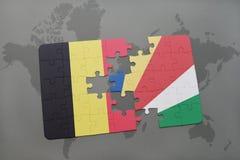 verwirren Sie mit der Staatsflagge von Belgien und von Seychellen auf einem Weltkartehintergrund Lizenzfreies Stockfoto