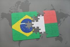 verwirren Sie mit der Staatsflagge von Brasilien und von Madagaskar auf einem Weltkartehintergrund Lizenzfreies Stockbild