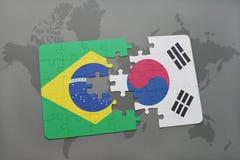 verwirren Sie mit der Staatsflagge von Brasilien und von Südkorea auf einem Weltkartehintergrund Lizenzfreie Stockbilder