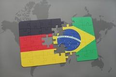 verwirren Sie mit der Staatsflagge von Deutschland und von Brasilien auf einem Weltkartehintergrund Stockfoto