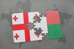 verwirren Sie mit der Staatsflagge von Georgia und von Madagaskar auf einer Weltkarte Lizenzfreie Stockfotos