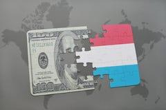 verwirren Sie mit der Staatsflagge von Luxemburg und von Dollarbanknote auf einem Weltkartehintergrund Stockfotografie