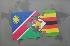 verwirren Sie mit der Staatsflagge von Namibia und von Simbabwe auf einer Weltkarte Lizenzfreie Stockbilder