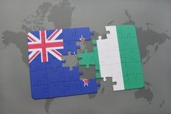 verwirren Sie mit der Staatsflagge von Neuseeland und von Nigeria auf einem Weltkartehintergrund Lizenzfreie Stockbilder