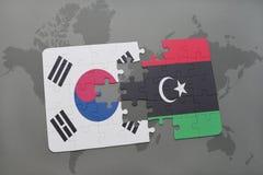 verwirren Sie mit der Staatsflagge von Südkorea und von Libyen auf einem Weltkartehintergrund Stockfotografie