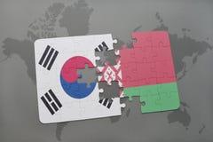 verwirren Sie mit der Staatsflagge von Südkorea und von Weißrussland auf einem Weltkartehintergrund Stockfoto
