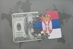 verwirren Sie mit der Staatsflagge von Serbien und von Dollarbanknote auf einem Weltkartehintergrund Stockfotografie