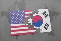 verwirren Sie mit der Staatsflagge von Staaten von Amerika und von Südkorea auf einem Weltkartehintergrund stockfotos