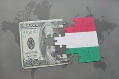 verwirren Sie mit der Staatsflagge von Ungarn und von Dollarbanknote auf einem Weltkartehintergrund Lizenzfreies Stockbild