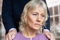 Verwirrte ältere Frau, die mit der Krise und Demenz getröstet wird vom Ehemann leidet lizenzfreie stockbilder