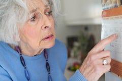 Verwirrte ältere Frau mit der Demenz, die Wandkalender betrachtet lizenzfreies stockbild