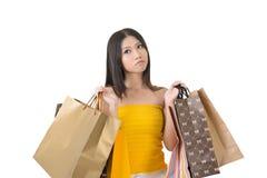 Verwirrte asiatische Frau, die Einkaufstaschen hält Stockfotografie