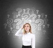 Verwirrte blonde Frau und Fragezeichen Stockbilder
