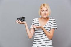 Verwirrte blonde junge Frau, die alte Weinlesefotokamera hält Stockbilder