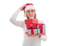 Verwirrte Blondine in Sankt-Hut, der Geschenke hält Stockfotos