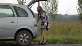 Verwirrte Frau öffnet Stamm und nimmt Werkzeuge Weiblicher Fahrer, Notfall und fahren Probleme, frustriertes Mädchen mit Ebene stock video