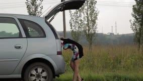 Verwirrte Frau öffnet Stamm und nimmt Werkzeuge Weiblicher Fahrer, Notfall und fahren Probleme, frustriertes Mädchen mit Ebene stock video footage