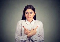 Verwirrte Frau, die auf unterschiedliche Arten zeigt lizenzfreie stockfotos