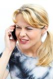 Verwirrte Frau, die an ihrem Handy plaudert Stockfotos