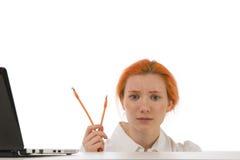 Verwirrte Frau, die versucht, ihren Laptop anzuschließen Stockfoto