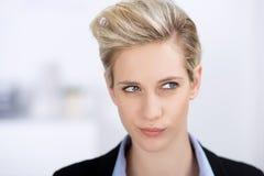 Verwirrte Frau, die weg im Büro schaut Stockfotos