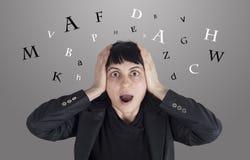 Verwirrte Frau mit Buchstaben um ihren Kopf Lizenzfreie Stockfotos