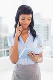 Verwirrte Geschäftsfrau, die einen Tabletten-PC verwendet Lizenzfreie Stockfotografie