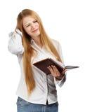 Verwirrte Geschäftsfrau mit persönlichem Organisator auf weißem backgro Lizenzfreie Stockbilder