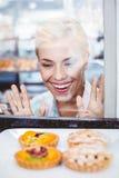Verwirrte hübsche Frau, die eine Fruchttorte durch das Glas betrachtet Stockbild