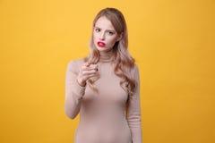 Verwirrte junge blonde Dame mit dem hellem Make-uplippenzeigen Lizenzfreie Stockfotos