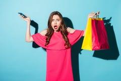 Verwirrte junge Brunettefrau, die Telefon und Einkaufstaschen hält stockbilder