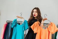 Verwirrte junge Frau, die zwischen zwei Kleidern wählt Stockfotos