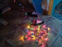 Verwirrte Kette von Weihnachtslichtern an der Unterseite an den Füßen einer Frau bei der Verzierung eines Weihnachtsbaums stockfotos