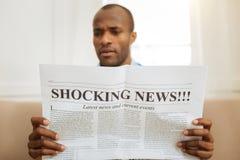 Verwirrte lesende schockierende Nachrichten des Mannes lizenzfreie stockbilder