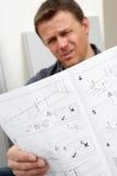 Verwirrte Mann-Lesemontage-Möbel-Anweisung Stockfoto