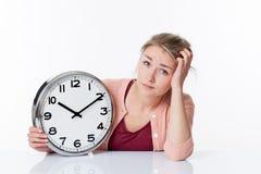 Verwirrte schöne junge blonde Frau, die eine Uhr anzeigt Lizenzfreie Stockbilder