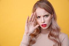 Verwirrte traurige junge blonde Dame mit den hellen Make-uplippen Lizenzfreies Stockfoto