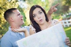 Verwirrte und verlorene Mischrasse-Paare, die draußen über Karte schauen Lizenzfreie Stockfotos