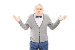 Verwirrter älterer Mann, der mit den Händen lokalisiert auf weißem backg gestikuliert Lizenzfreie Stockfotos