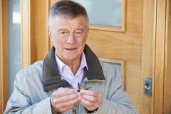 Verwirrter älterer Mann, der versucht, Tür-Schlüssel zu finden Stockfotos